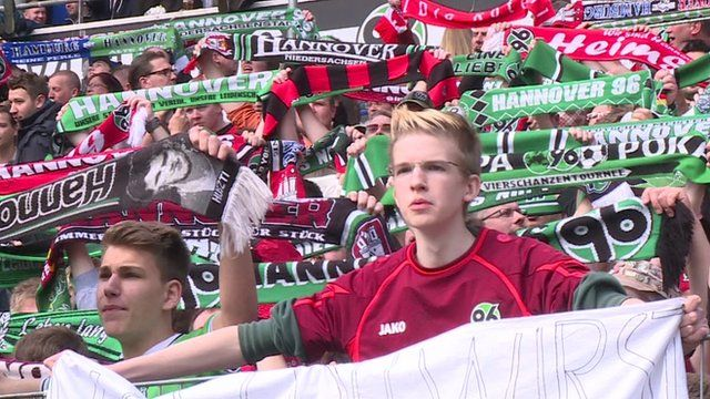 Football fans holding banners in Hanover, Germany