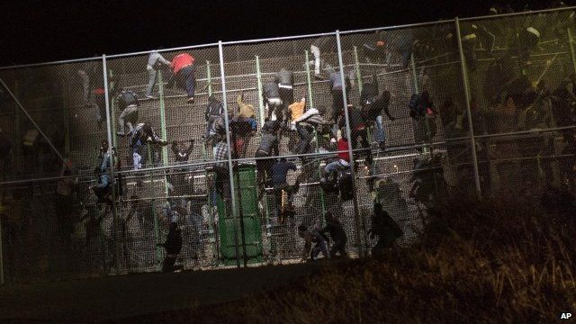 Sub-Saharan migrants scale a metallic fence that divides Morocco and the Spanish enclave of Melilla