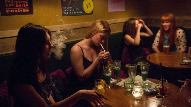 Girls smoke in a bar in central Moscow on May 30, 2014. Tough new anti-smoking legislation that comes into force on June 1