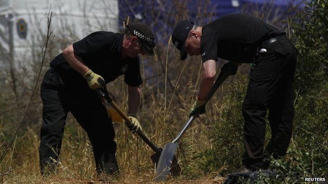 Two policemen searching scrubland