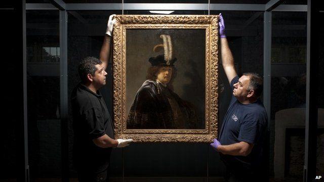 Two men hanging painting