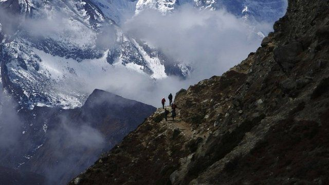 Trekkers walk in front of Mount Thamserku while on their way back from Everest base camp at Pheriche