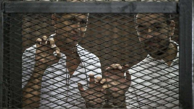 Al-Jazeera channel's Australian journalist Peter Greste (left) and Egyptian journalist Baher Mohamed stand inside the defendants' cage during their trial near Cairo's Tora prison, 1 June 2014
