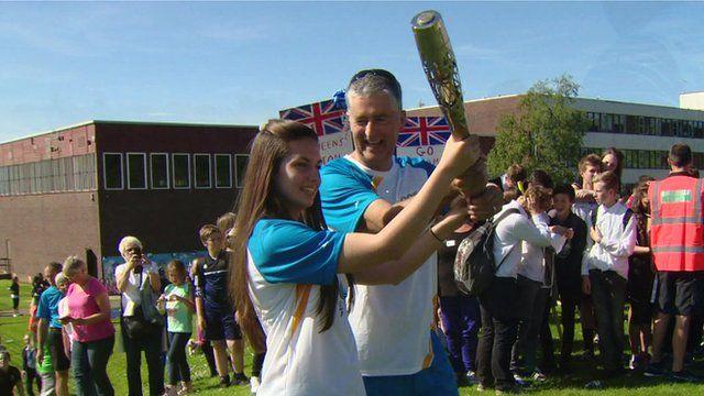 Student hands Queen's Baton to teacher Mr Foley at Newbattle High School