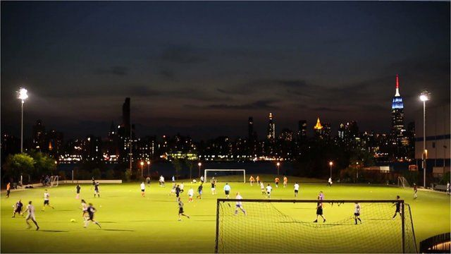A football field in Brooklyn with Manhattan skyline behind