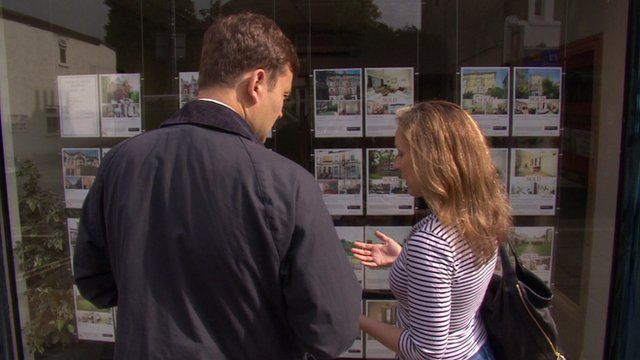 People looking in an estate agent window