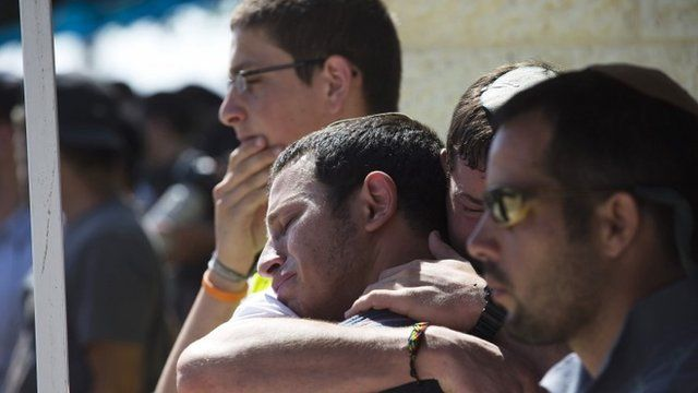 Friends and relatives mourn during a service for Gilad Shaar