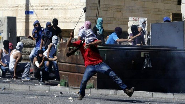Palestinian hurling stone towards police