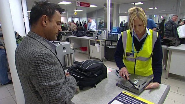 Airport security staff checking laptop