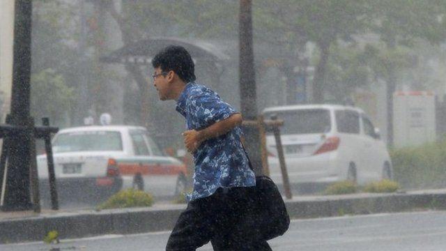 Man hurrying through rain and wind