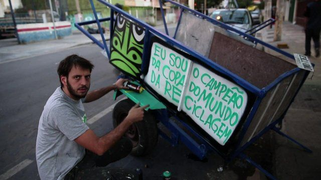 Thiago Mundano painting a trash cart