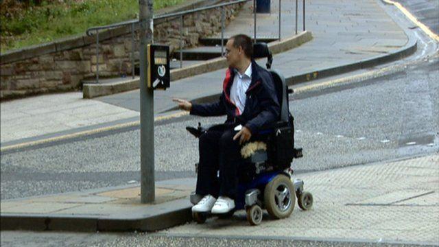 Man in a wheelchair at a pedestrian crossing