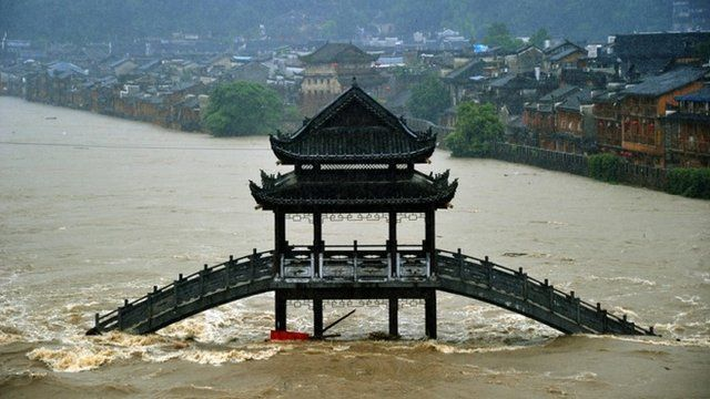 Buildings and a bridge are submerged by flood water at the Fenghuang Ancient Town on July 15, 2014