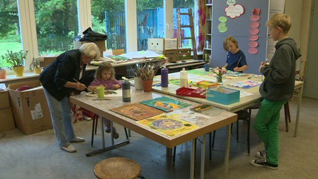 Older woman teaching children art