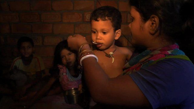 A young mother spoons oral rehydration therapy into a boy's mouth