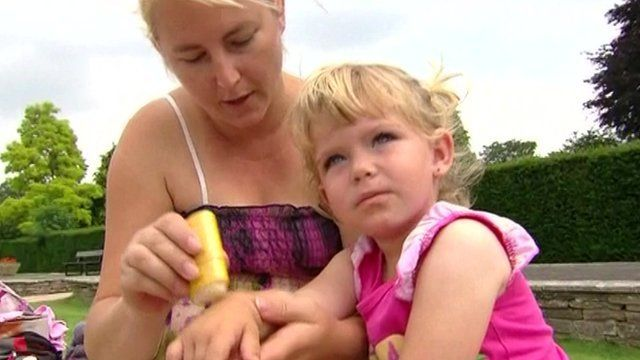 Woman putting sun cream on toddler