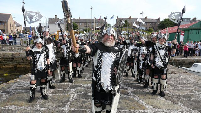 Alexander Johnson, dressed as a Viking, carries the Glasgow 2014 Queen's Baton through Lerwick on the Shetland Islands.