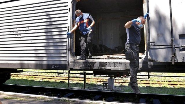 Dutch forensic experts jump from train holding bodies of MH17 crash