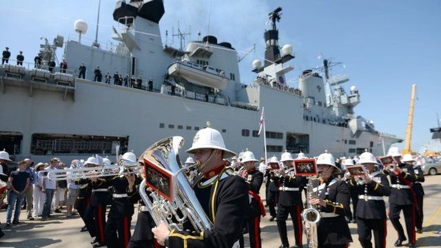 The band of The Royal Marines perform next to HMS Illustrious as she sails into her home port of Portsmouth for the final time ahead of being retired next month
