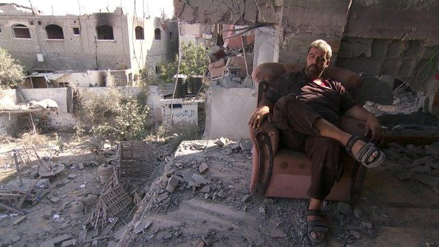 man sits in remains of his house