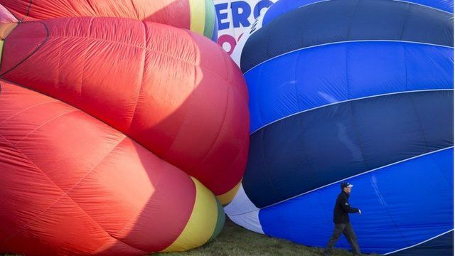 A man walks past inflating balloons at the International Balloon Fiesta near Bristol in western England August 8, 2014