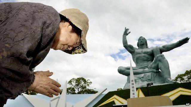 Woman prays at peace statue in Nagasaki