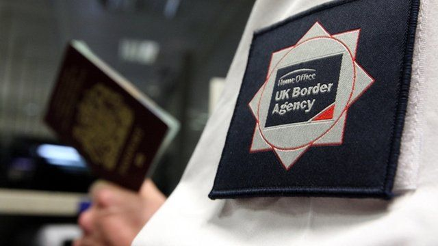 UK Border Agency man holding passport