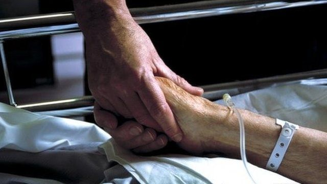 File: Holding patients hand