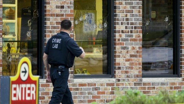 "A crime lab technician walks past bullet riddled windows at a Wendy""s in Omaha, Neb., Wednesday, Aug. 27, 2014"