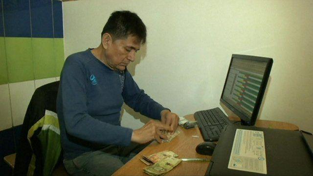 Prisoner/bank manger counting cash in Peruvian prison bank