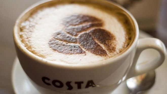 A Costa coffee cup with chocolate powder stencil of coffee beans