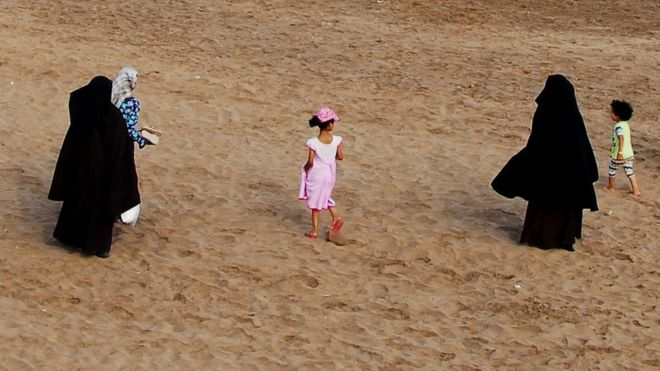 Two women wearing the niqab walk on the beach in Casablanca