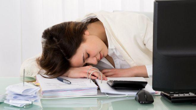 Mujer dormida en un escritorio