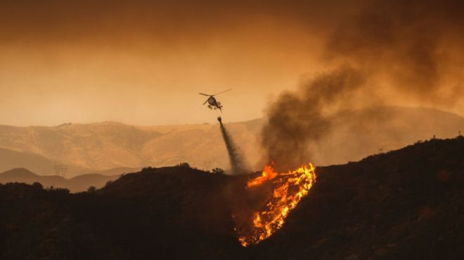 A firefighting helicopter drops water at the Sand Fire on July 23 2016 near Santa Clarita, California