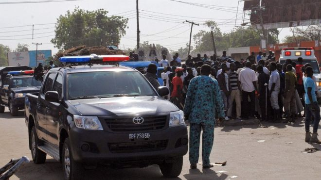 Emergency services, police and residents gather at scene of suicide bomb attack on a market in Maiduguri. 11 Dec 2016