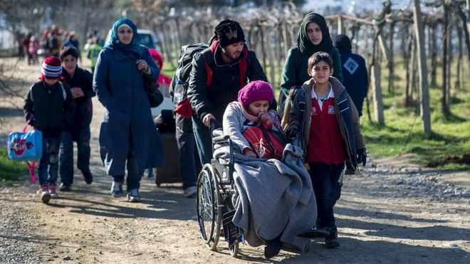 Migrants cross the Greek-Macedonian border near the town of Gevgelija on 25 February 2016
