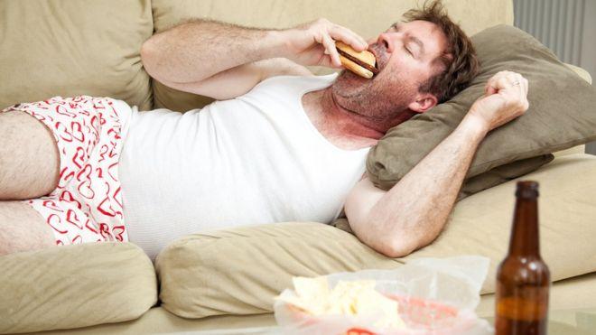 Divanda yatan bir adam hamburger yiyor.