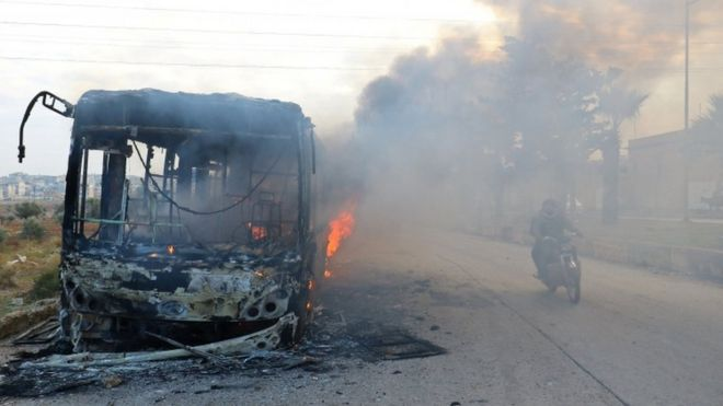 A man on a motorcycle drives past burning buses while en route to evacuate ill and injured people from the besieged Syrian villages of al-Foua and Kefraya, after they were attacked and burned, in Idlib province, Syria 18 December 2016