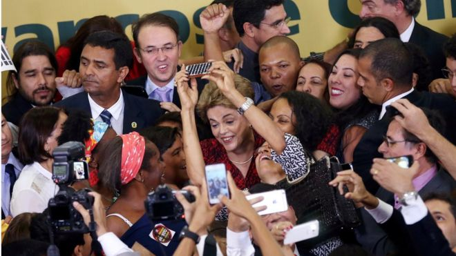 Dilma Rousseff surrounded by a tight crowd of people smiling and taking photos on their smartphones