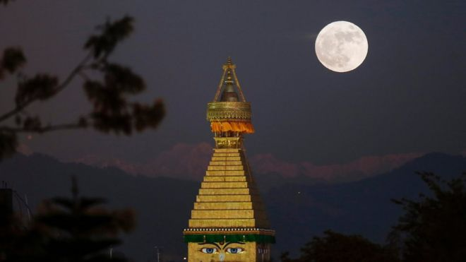 The moon rises over an upper portion of the Boudha stupa in Kathmandu, Nepal, 14 November 2016