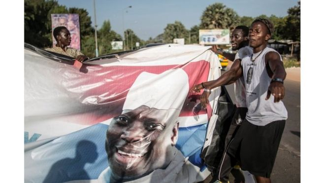 "Supporters of the newly elected Gambia""s President Adama Barrow tear down posters of the incumbent Yahya Jammeh in Serekunda on 2 December 2016."