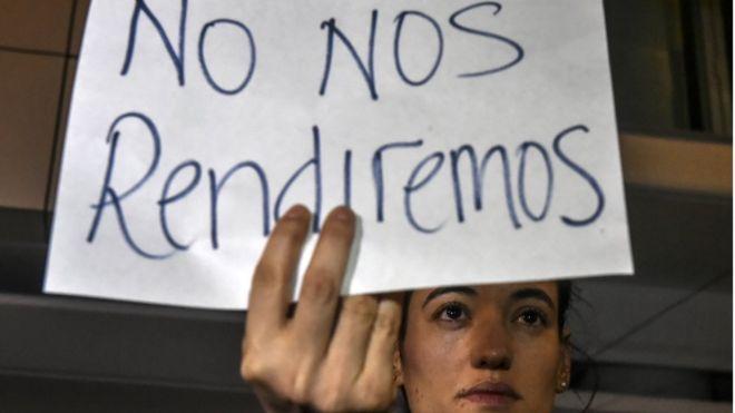 """Una joven sostiene un cartel: """"No nos rendiremos"""""""