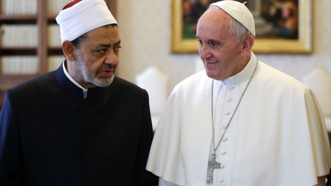 Sheikh al-Tayeb and Pope Francis standing side by side, in conversation