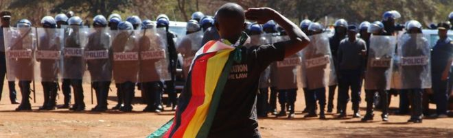 A demonstrator wrapped in a Zimbabwean flag salutes riot police in Harare - August 2016