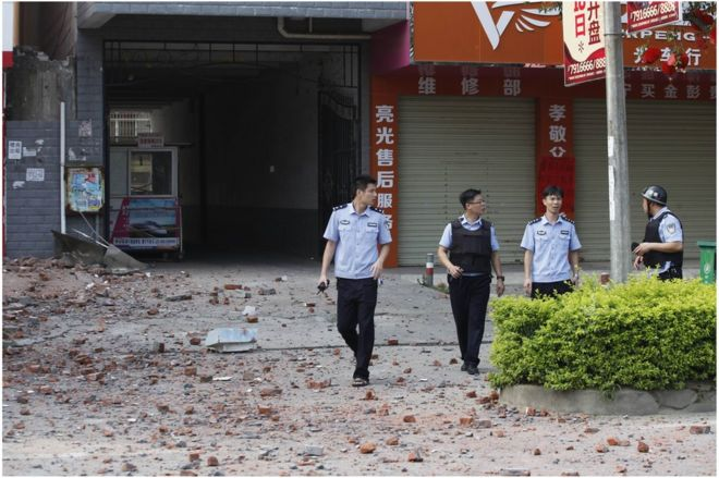 "Police investigators inspect the area around a damaged building a day after a series of blasts in Liucheng county in Liuzhou, south China""s Guangxi province on 1 October 2015."