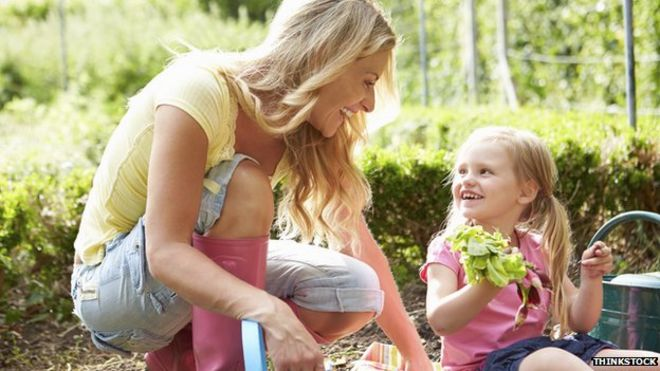 Mother and daughter smiling while gardening