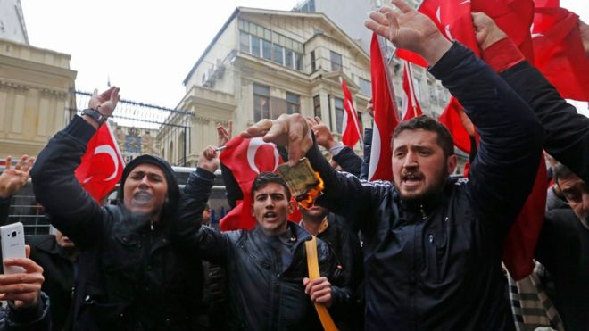 Supporters of Turkish President Recep Tayyip Erdogan burn a US dollar note as they shout slogans against the Netherlands in front of the Dutch Consulate in Istanbul, Turkey 12 March 2017