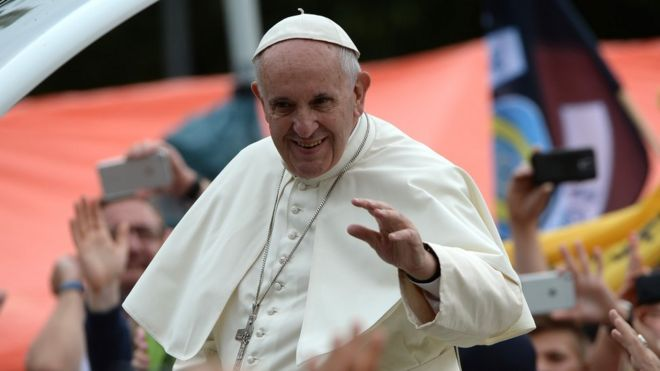 Pope Francis waves to crowds in Poland from the popemobile