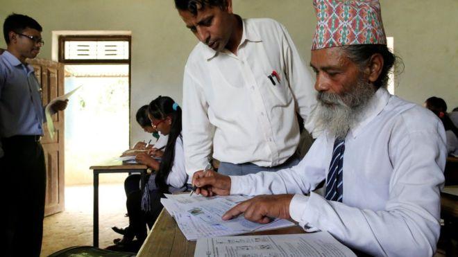 A teacher helps Durga Kami to fill an examination registration form