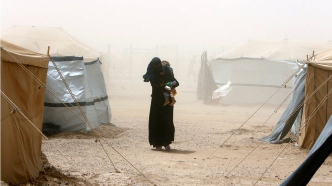 An Iraqi woman walks through a dust storm at a refugee camp outside Falluja
